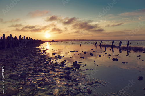 Foto op Aluminium Inspirerende boodschap Beautiful sunny red colorful sunset on the lake with stones, wooden posts and reflection, natural seasonal summer vacation background