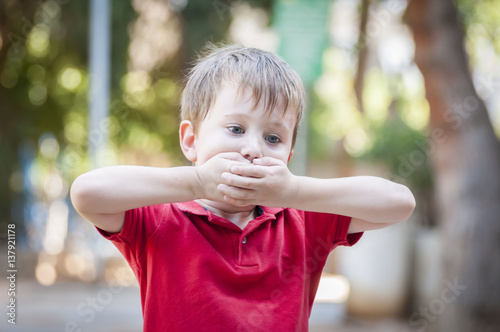 Photo  Serious little Caucasian boy closing his mouth with hands