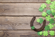 Background With Rusty Horseshoe And Paper Clover Leaves On The Old Wooden Boards. Space For Text.