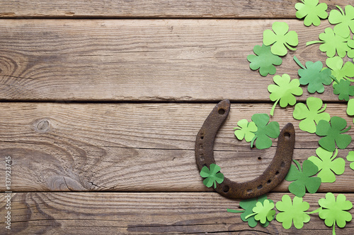 Valokuva  Background with rusty horseshoe and paper clover leaves on the old wooden boards