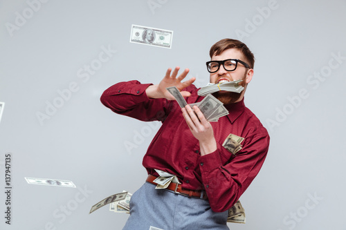 Fotografie, Obraz  Happy Male nerd playing with money