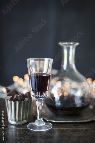 Port wine in a glass and a carafe with chocolate pralines
