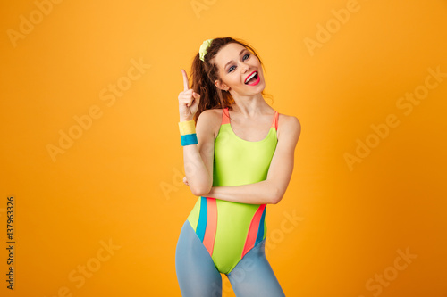 Fototapeta Smiling cute young woman athlete standing and pointing up obraz na płótnie