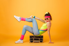 Playful Young Woman Athlete Sitting On Retro Boombox And Posing