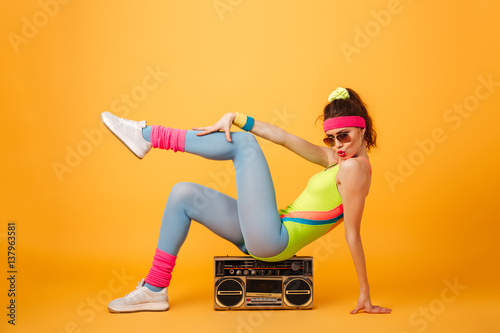 Fotografie, Obraz  Playful young woman athlete sitting on retro boombox and posing