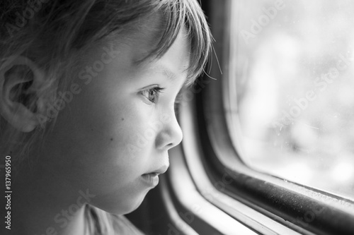 Monochrome Portrait Of A Beautiful Girl Who Looks In The Window Of The Train Close Up Of A Sad Child Looking Through Window Black And White Photography Buy This Stock Photo And