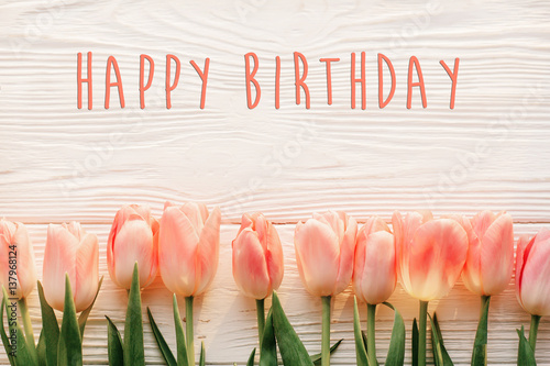 happy birthday text sign on pink tulips on white rustic wooden background flat lay Canvas Print