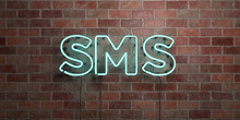 SMS - Fluorescent Neon Tube Sign On Brickwork - Front View - 3D Rendered Royalty Free Stock Picture. Can Be Used For Online Banner Ads And Direct Mailers..