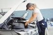 Female mechanic servicing car