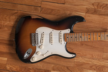 Vintage Fender Stratocaster Electric Guitar Sunburst Body And Worn Maple Neck Close Up Laid On A Wooden Surface