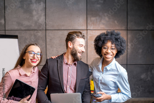 Fotografía  Portrait of three happy multi ethnic coworkers together at the office