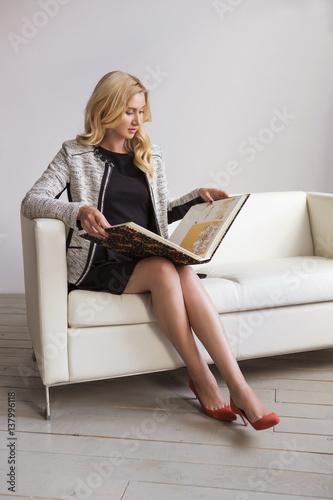 8428725b2e54 Blonde cute slim fit business woman in black dress and grey classic jacket  sitting on a couch looking on her album portfolio of works
