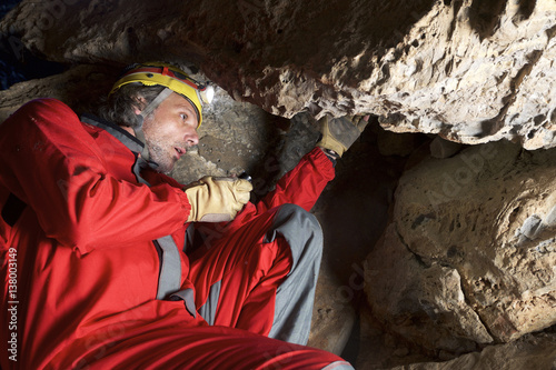 Low angle view of archaeologist working on rocks while sitting in cave