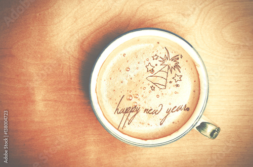 Cup of cappuccino coffee on wooden table. Words Happy New Year formed from coffee foam.