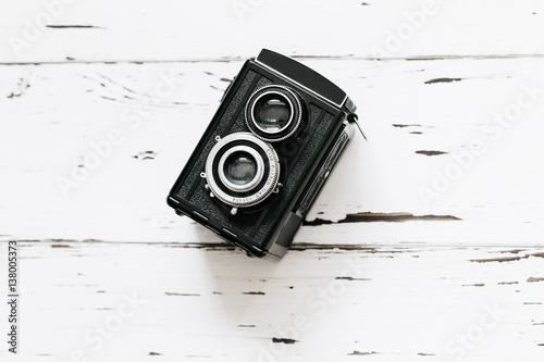 Stampe  Retro medium format camera on wood table background, vintage concept