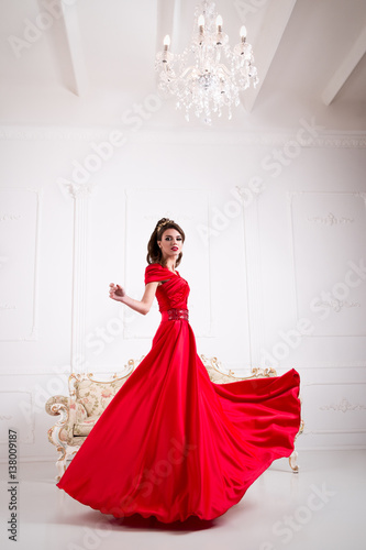 Elegant woman in a long red dress is standing in a white room chic, swirl dress Poster
