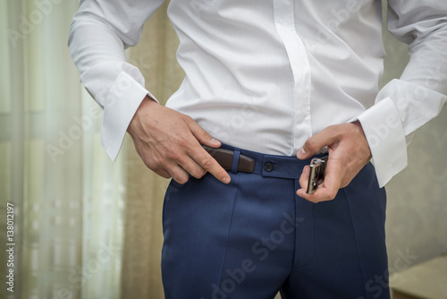 Fotografija  guy dresses a belt on his trousers in the room