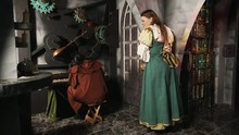 Smiling Woman In Medieval Costume Lay On Wall And Look With Admire At Sad Long Haired Man In Brown Monk Robe Playing Piano
