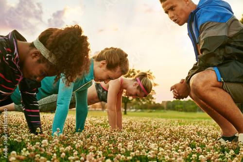 Fotografie, Obraz  Diverse group of women during a fitness training doing push-ups at sunset in nat
