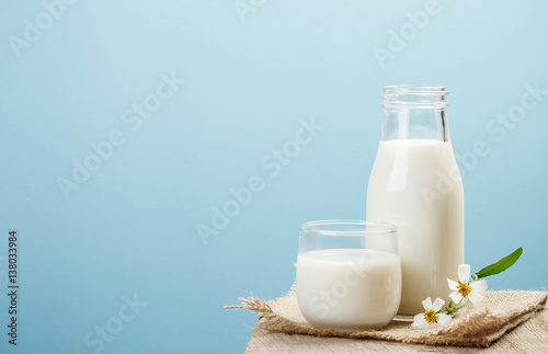 Fotografie, Obraz A bottle of milk and glass of milk on a wooden table on a blue background, tasty