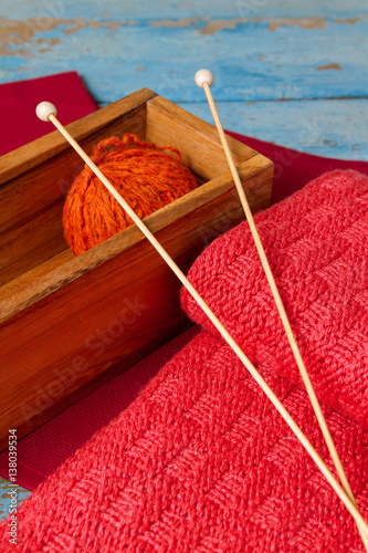 Photo  Skein of wool, spokes and a red knitted scarf