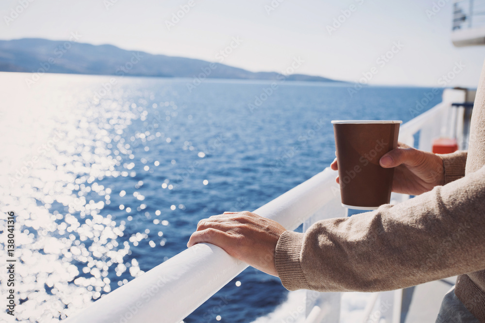 Fotografía  Traveller girl standing on ferry boat, looking at the sea and holding a coffee c