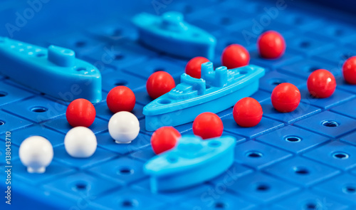 Foto Toy war ships and submarine are placed on the blue  playing Board