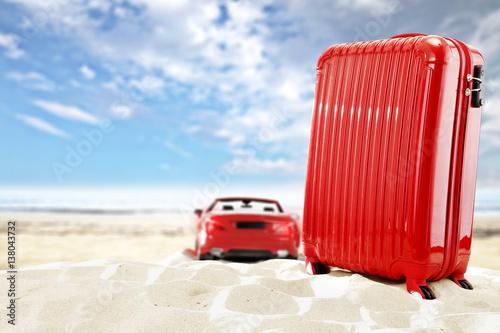 czerwona-walizka-na-tle-czerwonego-samochodu-na-plazy