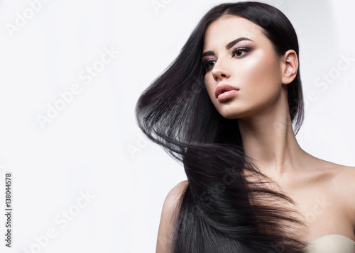 Beautiful brunette girl in move with a perfectly smooth hair, and classic make-up. Beauty face. Picture taken in the studio on a white background.