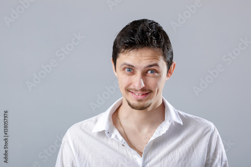 Fototapety, obrazy: young attractive smiling brunette man in white shirt on gray bac