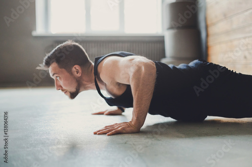 Fotografia  Young man fitness workout, push ups or plank