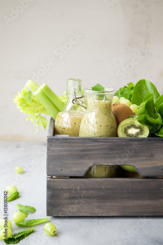Canvas Prints Fresh vegetables Green smoothie with apples, kiwi, grapes, lettuce romano and parsley in bottles and wooden box on gray marble background