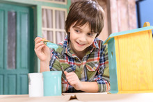 Cute Smiling Boy Holding Paintbrush While Painting Wooden Birdhouse On Table