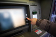Close up of hand entering pin at an ATM. Woman using banking machine.