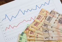 Stock Market And Business Concept Image. Data Analysis On Sales Or Stock Rates. Piles Of Mexican Pesos On The Chart.