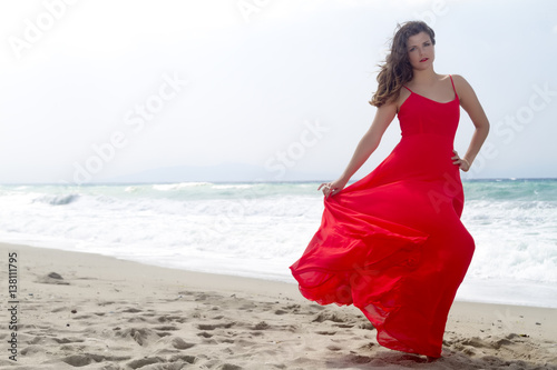 Deurstickers Akt Portrait of beautiful woman in red dress in front of the beach.