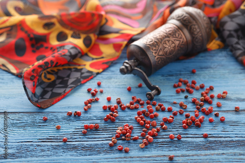 Fotografía  Red pepper on blue wooden table with silk scarf