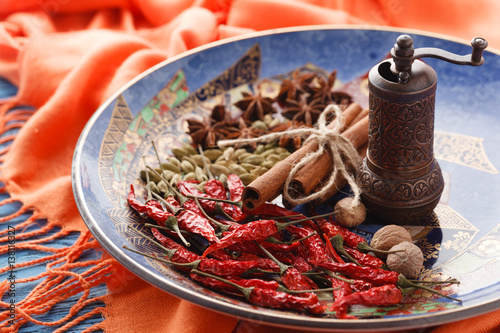 Full plate of asian spices with chilli on blue table