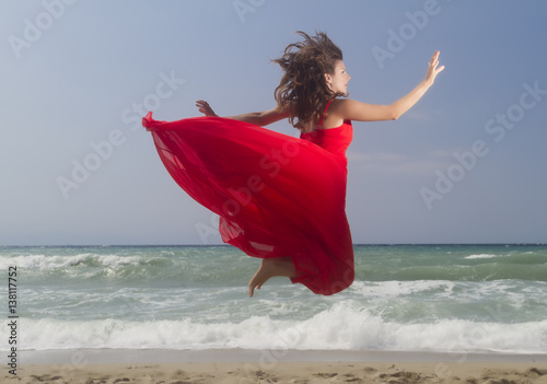 Deurstickers Akt Portrait of beautiful woman jumping in red dress in front of the beach.