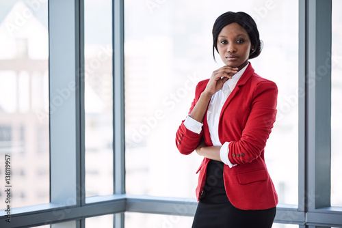 Confident businesswoman looking at the camera with bold body language while wearing a red blazer with large windows behind her in the background Canvas Print