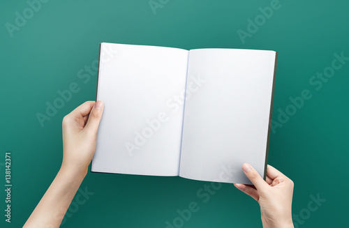 Fotografering  Woman hands holding a blank book for reader with copy space at green background