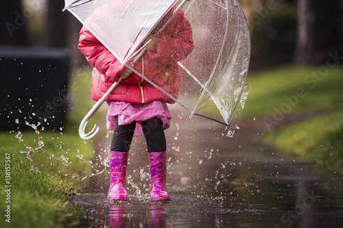 Fotografie, Obraz  A young girl is playing in the much needed California rain.