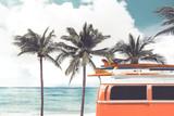 Vintage samochód zaparkowany na tropikalnej plaży (nad morzem) z deską surfingową na dachu - Wypoczynek w lecie. efekt koloru retro - 138167374