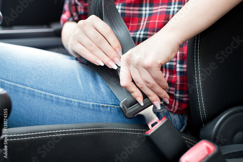 Photo  Woman fastening seat belt in car