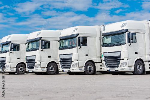 Plakat Transport - Cztery białe ciężarówki zaparkowane na podwórzu w linii