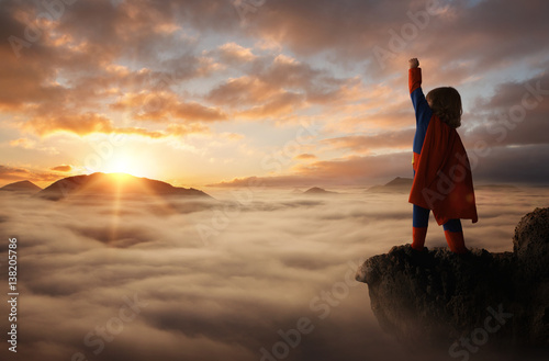 Fotografie, Tablou Little boy acting like a superhero on top of the mountain at sunset with copy sp