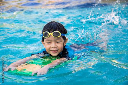 Photo  boy learn to swim in the swimming pool