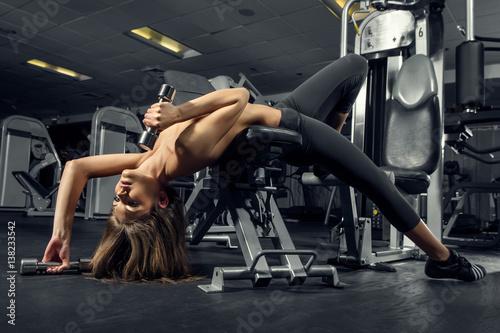 Obraz fitness, siłownia, kobieta, sportowiec - Młoda dziewczyna trenuje na siłowni z cięzarkami - fototapety do salonu