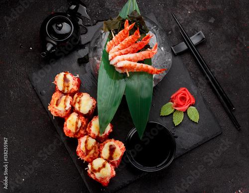 kuchnia-japonska-pieczone-sushi-rolls-i-krewetkowe-szaszlyki-na-kamieniu-na-czarnym-tle-betonu
