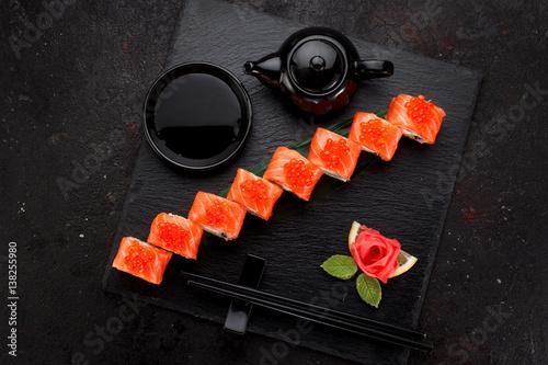 sushi-umaki-z-lososiem-i-kawiorem-ulozone-pod-katem-podane-z-herbata-na-czarnym-betonowym-kwadratowym-naczyniu